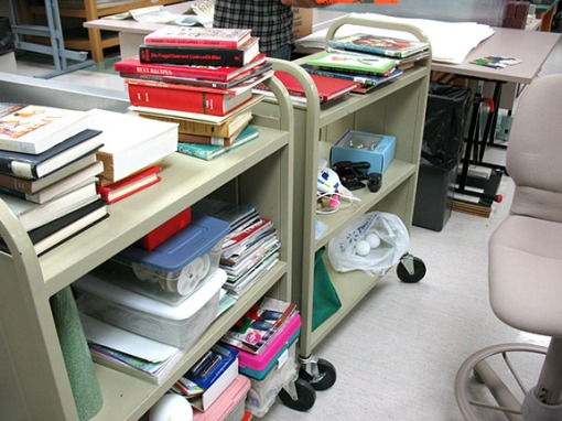 "A bookcart overflowing with craft supplies and materials to be ""upcycled."""