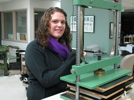 Ashley clamps down adhesive bindings in a book press.