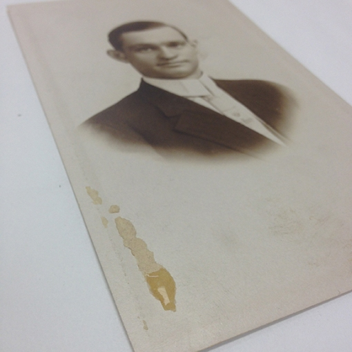 Using a methyl cellulose poultice to remove an accretion on the recto of a photograph.