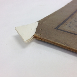 A board edge made of archival board being fitted into the backing board of a photograph.