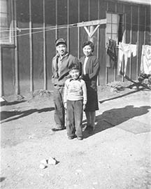 Saichi, Suzuyo, and Eddie Seo in front of barrack at Heart Mountain Relocation Center.