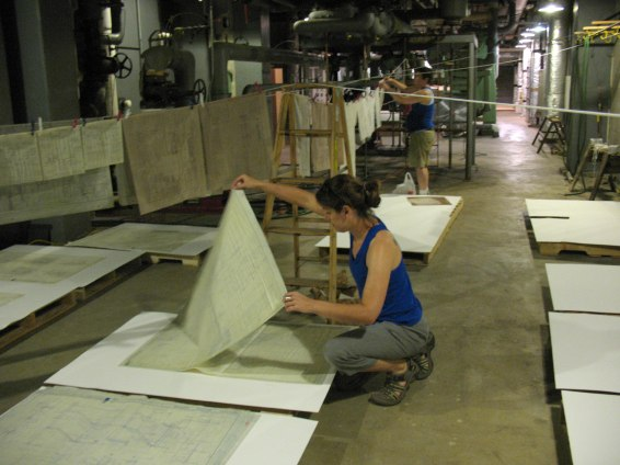 Conservator Melissa Tedone laying out wet architectural drawings during the 2010 flood in Ames