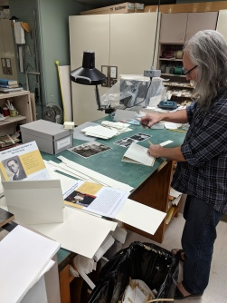 Conservation technician Jim Wilcox working on photo mounts for the exhibit.