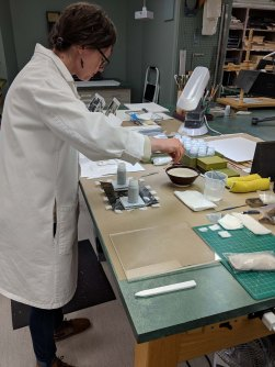 Collections conservator Sonya Barron working on attaching tissue hinges to a photo.