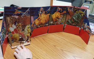 Photo of a pop-out book open to show 3D nature of book. Features a rodeo with a bull and cowboy on horse in an arena.