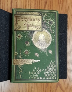 A photo of the front cover of a casebinding that has been block stamped with gold, red, and yellow. The design includes sun and moon graphics as well as leaves, wavy lines that possibly depict a river, and Tennyson's portrait.